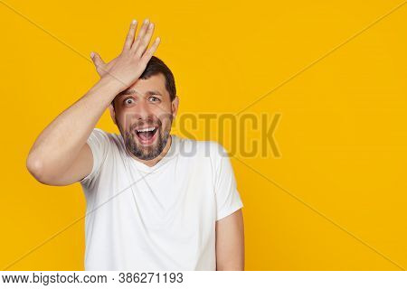 Young Man With A Beard In A White T-shirt, Surprised, Put His Hand On His Head For A Mistake, Rememb