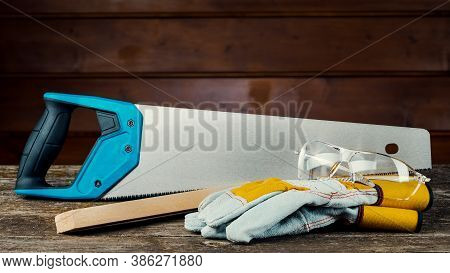 Hand-held Wood Hacksaw With Blue Handle Close-up. Hand Saw For Sawing Trees On A Wooden Background.