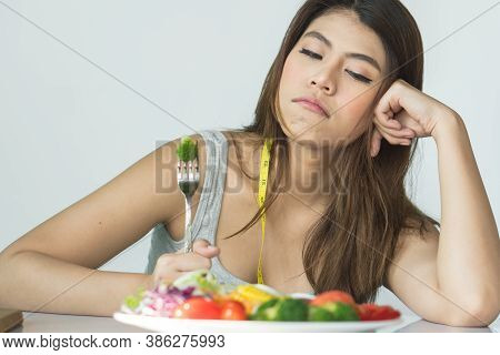 Asian Women Is On Dieting Time Looking At Broccoli On The Fork. She Does Not Want To Eat Vegetables