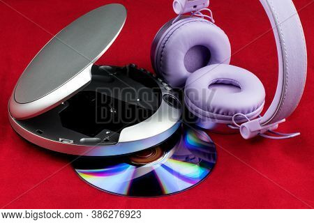 Cd And Cd Player And Headphones Isolated On A Red Background
