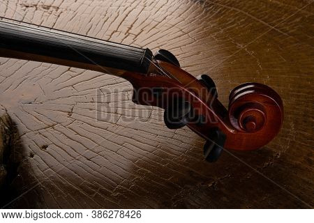 Details Of An Old And Beautiful Violin On A Rustic Wooden Surface And Black Background, Low Key Port