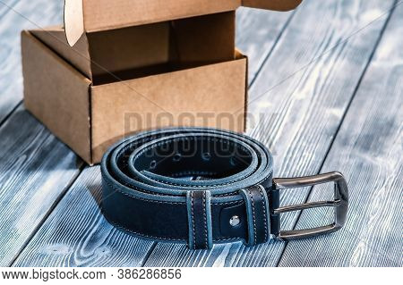Belt With Metal Buckle. The Belt Is Rolled Up, Next To A Gift Box. Template For The Design Of Leathe