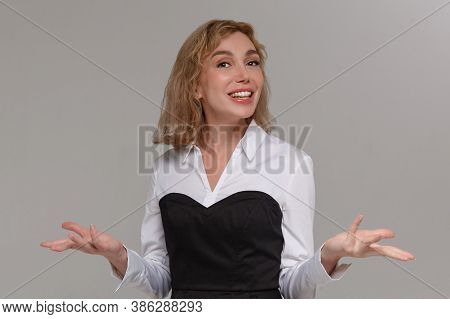 Carefree Happy Clueless Young Woman Shrugging With Hands Spread Aside Smiling. Teenager Having No Id
