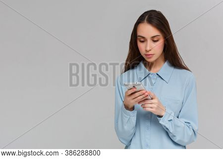 Content Teenager With Long Hair, Holds Modern Cell Phone, Scrolls Through Social Networks, Has Cheer
