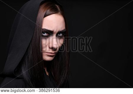 Mysterious Witch With Spooky Eyes On Black Background, Space For Text