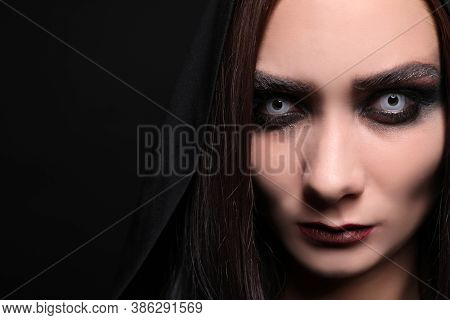 Mysterious Witch With Spooky Eyes On Black Background, Closeup. Space For Text