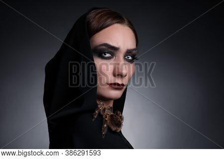 Mysterious Witch With Spooky Spider On Dark Background
