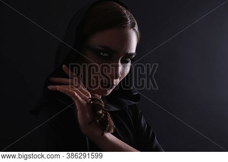 Mysterious Witch With Spooky Spider On Black Background, Space For Text