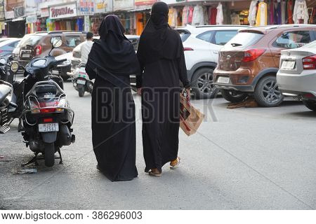 Two Females Wearing Islamic Niqab Veil And Black Jacket Are Shopping At The Market. Udaipur India -