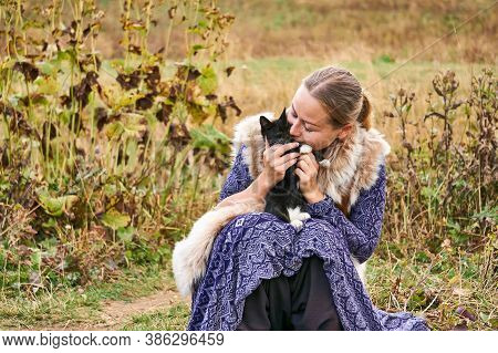Adygea, Russia - September 08, 2020: Young Woman Dressed In Ethnic Style With A Kitten In Her Arms C