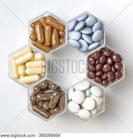 Various Capsules And Pills With Dietary Supplements Or Medicines In Hexagonal Jars