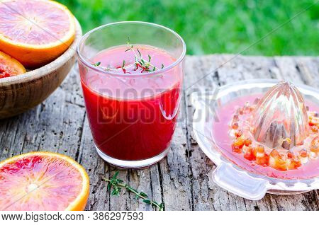 Glass With Fresh Made Sicilian Blood Orange Juice On Old Wooden Textured Table On Green Grass Backgr