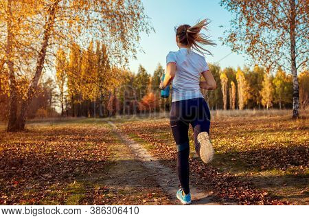 Runner Training In Autumn Park. Young Woman Running At Sunset In Sportive Clothes. Active Lifestyle.
