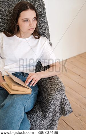 Young Woman In Jeans And White T-shirt Sits In Gray Armchair And Reads Paper Book. Concept Of Relaxi