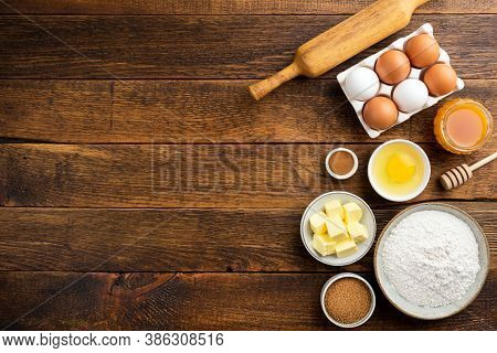 Cooking Baking Ingredients On A Wooden Table Background. Flour Eggs Butter Sugar And Other Pastry In