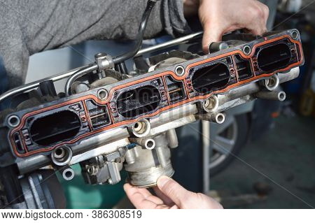 A Car Mechanic In A Gray Work Suit Holds An Exhaust Manifold With A Throttle Removed From An Automob