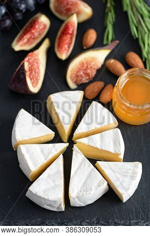 Camembert Or Brie Cheese With Figs, Honey And Almonds On Black Slate Board