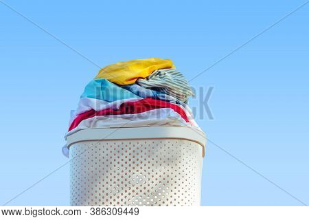 Laundry Basket Full Of Clothes.on A Blue Background