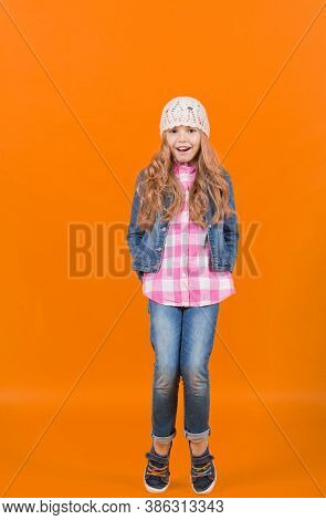 Child Model With Long Blond Hair Smile And Stand Tiptoe. Girl In Jeans Suit, Hat, Plaid Shirt On Ora