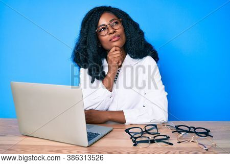 Beautiful african woman at the oculist clinic thinking concentrated about doubt with finger on chin and looking up wondering
