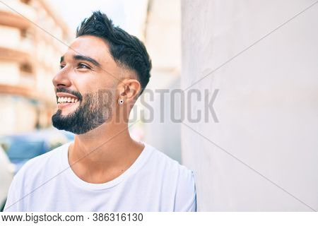 Young arab man smiling happy leaning on the wall at the city.