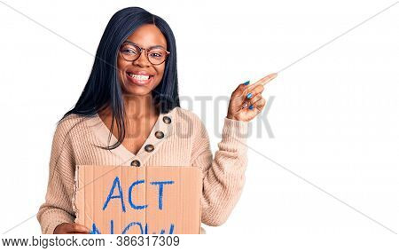 Young african american woman holding act now banner smiling happy pointing with hand and finger to the side