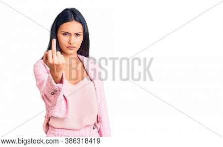 Young beautiful latin girl wearing business clothes showing middle finger, impolite and rude fuck off expression
