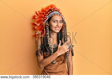 Young brunette woman wearing indian costume cheerful with a smile of face pointing with hand and finger up to the side with happy and natural expression on face