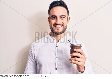 Young handsome man with beard drinking mate infusion beverage over white background looking positive and happy standing and smiling with a confident smile showing teeth