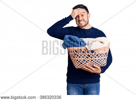 Young handsome man holding laundry basket stressed and frustrated with hand on head, surprised and angry face
