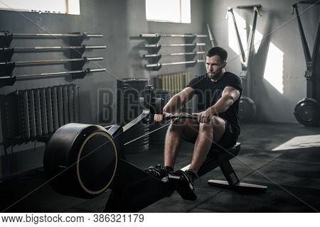 Focused Man Train on Rowing Machine .