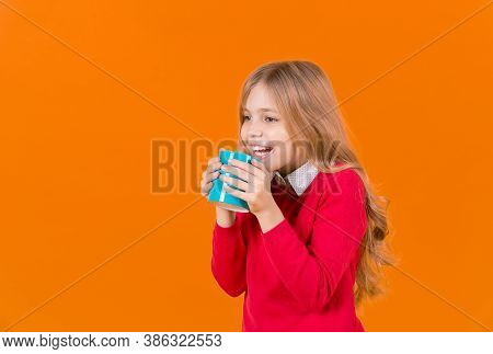 Child Smile With Blue Cup On Orange Background. Thirst, Dehydration Concept. Health And Healthy Drin