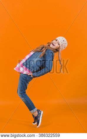 Child In Jeans Suit, Hat, Plaid Shirt Balance Tiptoe. Girl Model With Long Blond Hair Smile On Orang