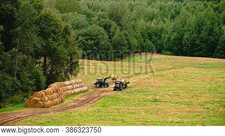 Bales Of Hay Are Loaded Onto A Trailer By A Tractor In Countryside During The Summer Season, Tractor