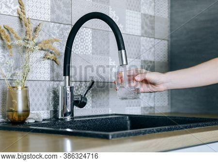 Human Hand Holding Glass Pouring Fresh Drink Water At Kitchen Faucet