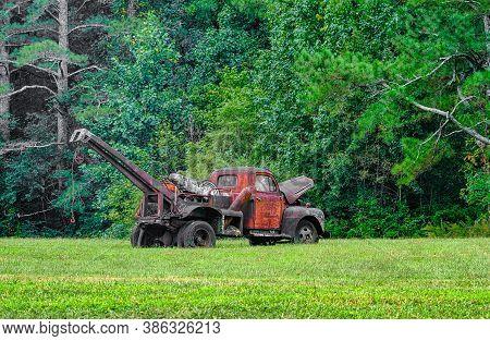 An Old Rusty Wrecker In Field Near Summer Woods