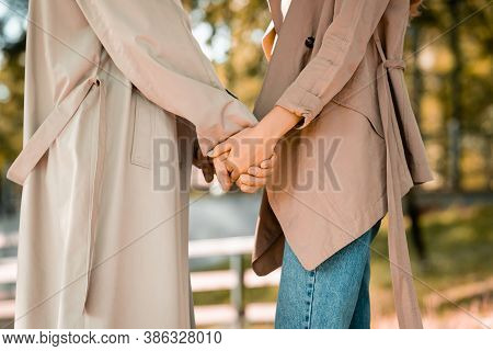Partial View Of Man And Woman In Trench Coats Holding Hands In Park