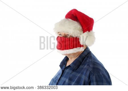 A man wearing a Santa Claus Hat and Red Velvet Santa Claus Style Face Mask to protect himself from Covid-19. Isolated on white. Room for text. Coronavirus is dangerous be safe and wear your mask.