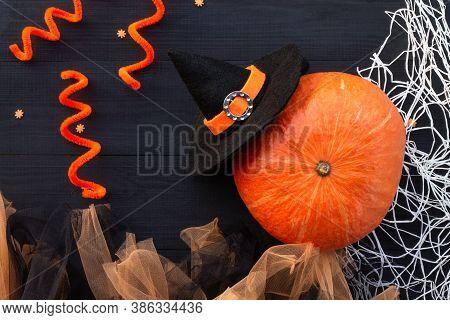 Orange And Black Halloween Flatlay. Pumpkin, Tulle, Witch Hat, Spider Web On A Black Wood Background