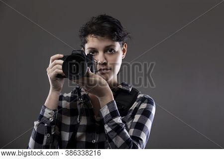 Young Female Photographer Holding A Camera In A Studio.  She Is Posed And Lit So The Background Can