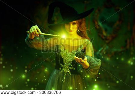 Magic Halloween. Enchanting young witch casts a spell with a thread and a spindle in an old castle. Fairy tales.