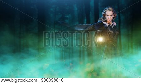 Magic Halloween. Enchanting young woman witch conjures in a dark night forest. Copy space.