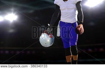 Football Player Holding Ball And Helmet Under Bright Spotlights