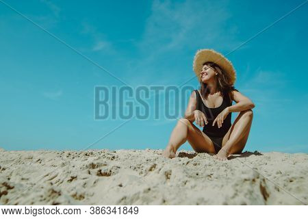 Woman At Sand Beach In Black Swimsuit Blue Sky On Background