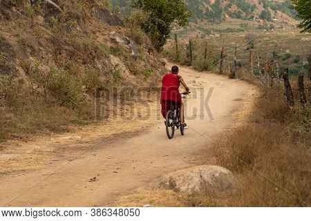 A Monk Riding On Bicycle At A Remote Place In Bhutan.