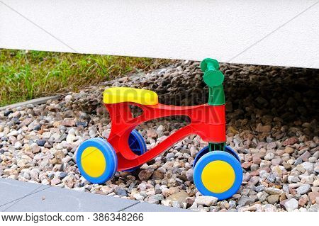 Childrens Plastic Colorful Tricycle On A Gravel In A Playground In The Yard At Summer Day.