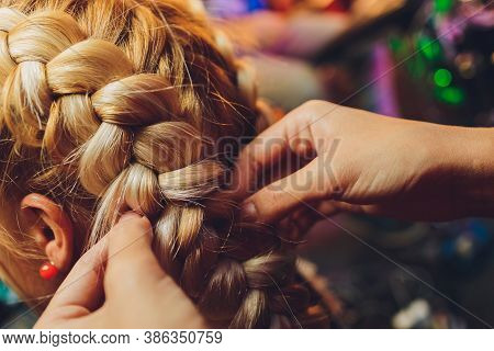 Process Of Braiding The Master Weaves Braids On Her Head Blond Little Girl In Beauty Salon Close Up.