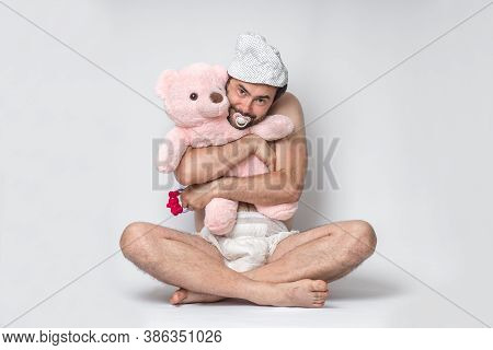 Infant Adult Man With Pacifier In Diaper Holding Pink Teddy Bear. Big Baby.