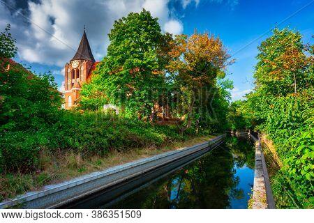Beautiful brick church in Pruszcz Gdanski over the Radunia canal, Poland