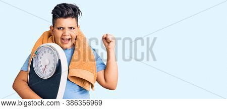 Little boy kid holding weight machine to balance weight loss screaming proud, celebrating victory and success very excited with raised arms